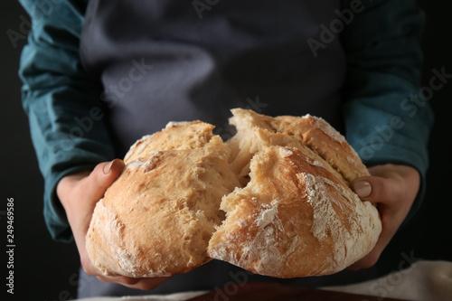 Fotobehang Brood Young woman breaking freshly baked bread on dark background, closeup
