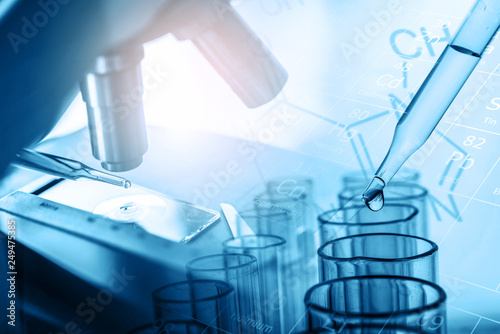 microscope and dropping chemical liquid to test tubes with lab glassware, science laboratory research and development concept in blue tone