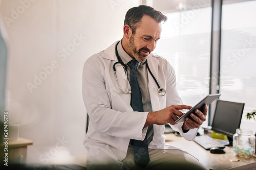 Fotografia  Doctor using digital tablet at his clinic