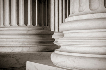 Abstract close-up of the neoclassical white marble fluted columns at the entrance to the US Supreme Court Building in Washington DC