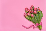 Fototapeta Tulipany - Pink tulips bouquet decorated with ribbon on pink background. Copy space, top view