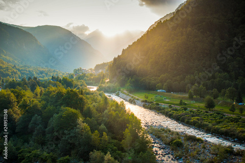 Fotografie, Tablou Golden hour on Sesia river valley with sun rays filtering through the clouds
