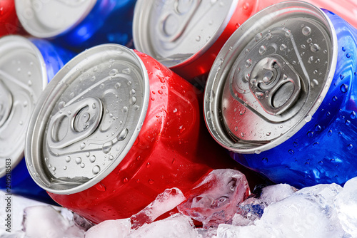 Fotografia Red and blue soda cans on ice with condensation droplets