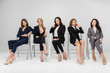 woman in formal wear sitting with crossed legs near female coworkers isolated on grey