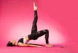 canvas print picture - Long haired beautiful pilates or yoga athlete does a graceful pose while wearing a tight sports outfit against a pink background in a studio