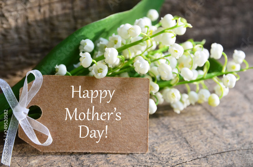 Poster Muguet de mai Bouquet of lilies of the valley with Happy Mother´s Day tag card on wooden background.Lily-of-the-valley flowers. Mothers Day festive concept with copy space.Selective focus.