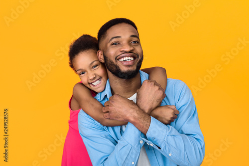 Photo  Little girl hugging father, having fun over background