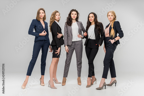 Fotografiet  beautiful successful women standing with hands in pockets on grey background