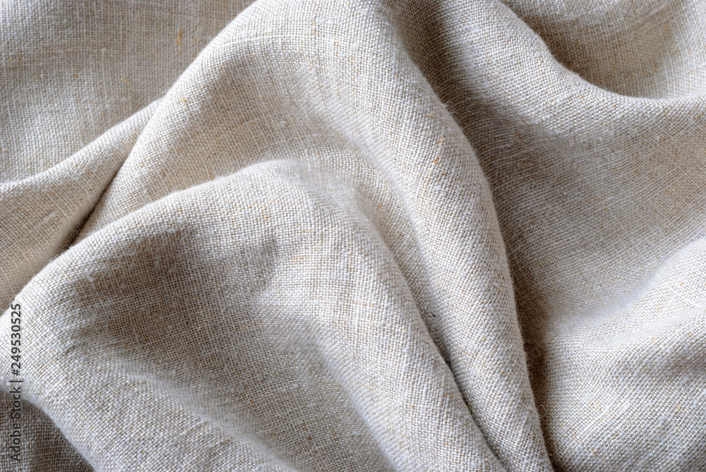 Fototapeta Gathered and folded texture of woven linen fabric