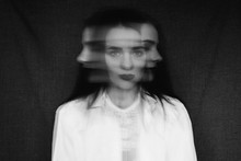 Crazy Portrait Of Girl With Mental Disorders And Split Personality. Black And White With Added Grain And Motion Blur