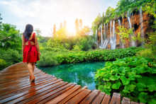 Woman Traveler Walking On Wooden Path Trail With Lakes And Waterfall Landscape In Plitvice Lakes National Park, UNESCO Natural World Heritage And Famous Travel Destination Of Croatia.