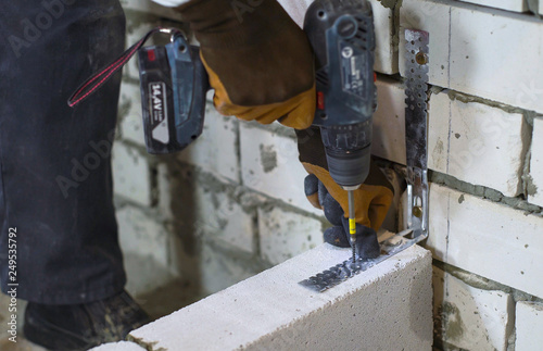 builder screwing joining clamp in aerated concrete block with electric drill Canvas Print