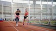 Two young women start running in indoors sports arena
