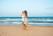 Euphoric young couple meeting and hugging on the sea beach. Horizontal shape, side view, copy space..Happy lovers.
