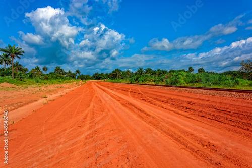 Montage in der Fensternische Ziegel Typical red soils unpaved rough countryside road in Guinea, West Africa.