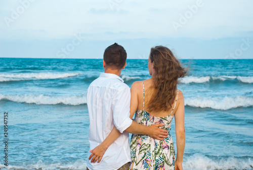 Fotografía  Couple On Beach Summer Vacation, Lovers looking to the horisont of the sea and hugging