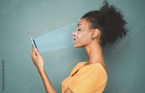 Woman with smartphone using face ID recognition system Wallpaper Mural