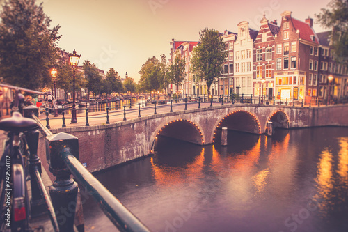 View of the City of Amsterdam with canal and bridge seen at sunset with vintage Canvas Print