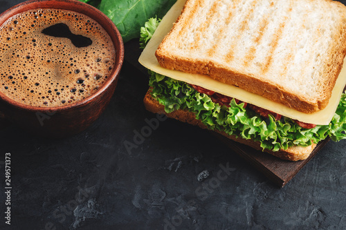 Keuken foto achterwand Snack Cup with hot coffee and sandwich with grilled toast, salami sausage, salad lettuce, spinach leaves and cheese on a dark background