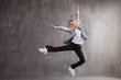 canvas print picture - Successful businesswoman. Young blonde woman in business suit and sneakers jumping for joy,