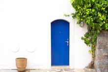 Traditional Greek Blue Door With White Wall, Plant And Terra Cota Vase