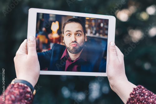 Fotografia  Young woman using a tablet, having a video call chat with her businessman boyfriend who is sending her kisses while he's away on a business trip