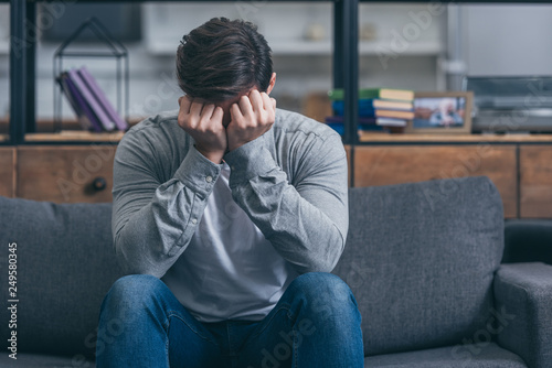 Photo man sitting on couch, crying and and covering face with hands at home