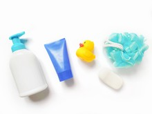Flat Lay Bath Products Photo. Liquid Soap Packaging, Purple Cream Tube, Yellow Rubber Duck, Blue Sponge And Soap Bar. Items For Personal Care, Natural Organic Cosmetics