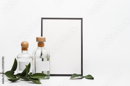Poster de jardin Spa Wooden frame in the composition of glass bottles and fresh green leaves on a white table. The concept of spa treatments and body care. Mockup.