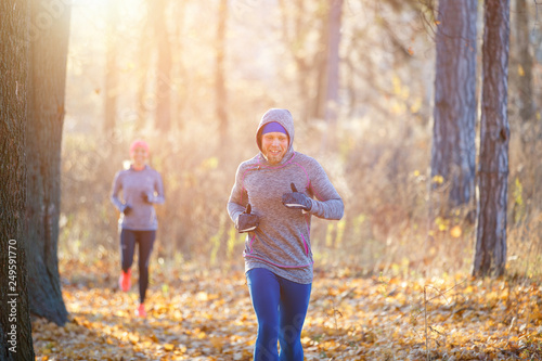 Fotografia  Young man and woman jogging on park trail