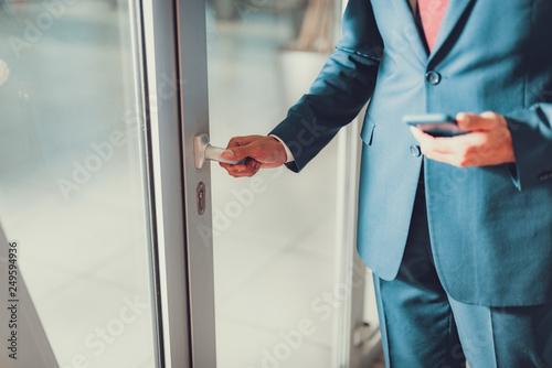 Foto  Man opening glass door in his office