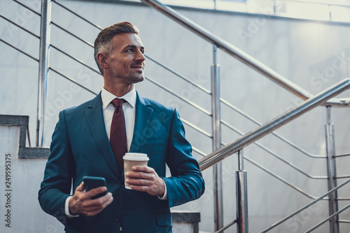 Fotografia  Smiling man with beverage and telephone looking aside