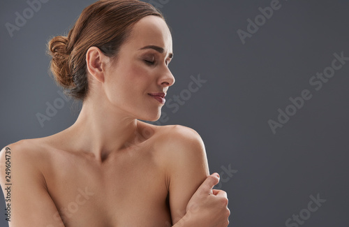 Fotomural Charming young woman closing eyes and hugging herself