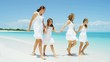 Caucasian mother and daughters walking on a Caribbean beach