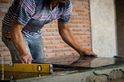 Fototapeta Men work laying tile, ceramic obraz na płótnie