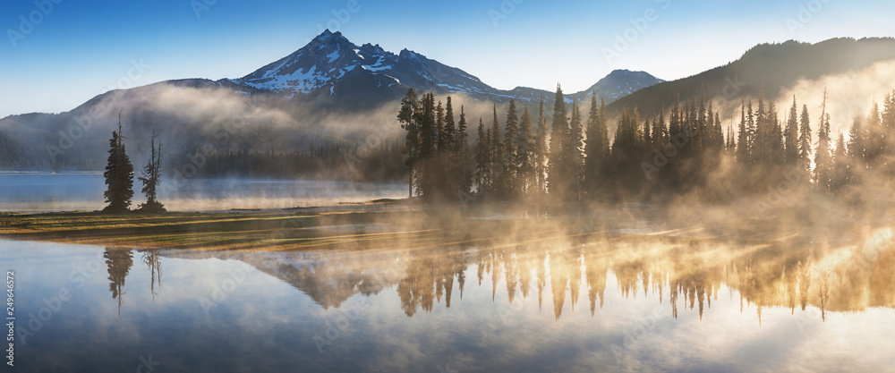 Fototapeta South Sister and Broken Top reflect over the calm waters of Sparks Lake at sunrise in the Cascades Range in Central Oregon, USA in an early morning light. Morning mist rises from lake into trees.
