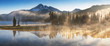 Leinwandbild Motiv South Sister and Broken Top reflect over the calm waters of Sparks Lake at sunrise in the Cascades Range in Central Oregon, USA in an early morning light. Morning mist rises from lake into trees.