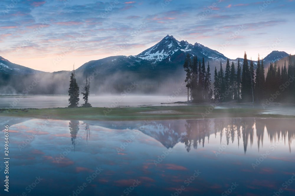 Fototapety, obrazy: South Sister and Broken Top reflect over the calm waters of Sparks Lake at sunrise in the Cascades Range in Central Oregon, USA in an early morning light. Morning mist rises from lake into trees.