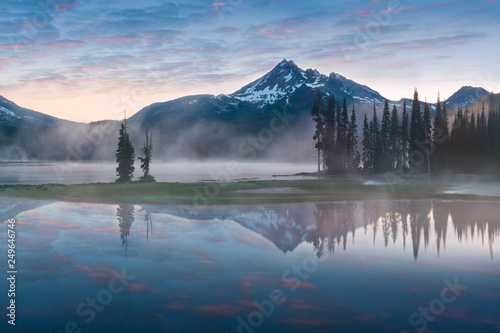 Fotobehang Bergen South Sister and Broken Top reflect over the calm waters of Sparks Lake at sunrise in the Cascades Range in Central Oregon, USA in an early morning light. Morning mist rises from lake into trees.