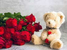 Background Valentines Day Flower Bouquet And Teddy Bear. A Bouquet Of Red Roses And A Small Teddy Bear. Greeting Card For The Holiday, A Card About Love, Happy Birthday.