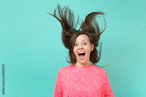 Valokuva  Amazed young woman in knitted pink sweater with fluttering hair keeping mouth wide open, looking surprised isolated on blue background