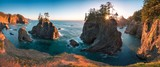 Sunset at Natural Bridges along Samuel H. Boardman State Scenic Corridor, Oregon during a golden hour - sunbeams through trees with dense vegetation. Beautiful seascape with rocks. West Coast USA