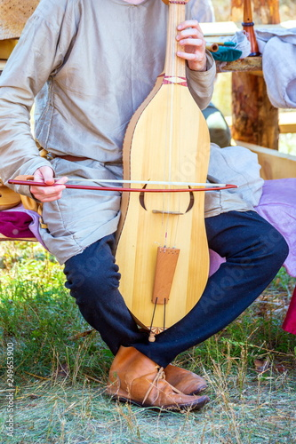 Fotografia  Russia, Samara, August, 2018: A young man plays an ancient stringed instrument