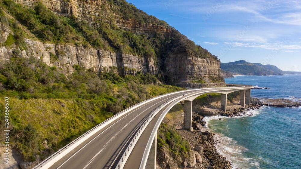 Fototapeta Travelling on the sea cliff bridge coastal drivel along the pacific ocean. Grand pacific drive, East coast of Australia. Clear sunny day.