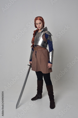 Photo full length portrait of a  red haired girl wearing medieval warrior costume and steel armour, standing pose facing away from the camera on grey studio background