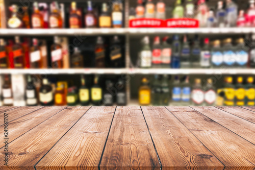 Cuadros en Lienzo Wood table top and wine Liquor bottle on shelf blurred background