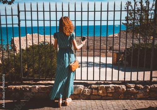Carta da parati Girl taking a picture with a smartphone in Ancient roman amphitheater of Tarragona, Spain