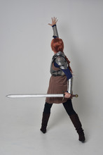 Full Length Portrait Of A  Red Haired Girl Wearing Medieval Warrior Costume And Steel Armour, Standing Pose Facing Away From The Camera On Grey Studio Background.