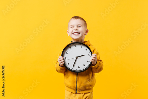 Obraz Little kid boy 3-4 years old wearing yellow clothes hold clock isolated on orange wall background, children studio portrait. People sincere emotions, childhood lifestyle concept. Mock up copy space. - fototapety do salonu