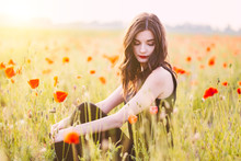 Beautiful Young Woman At A Poppy Field In Summer Sunset